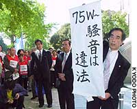 A lawyer for residents suing the government over noise from Atsugi base displays a sign in front of the Yokohama District Court stating that sound exceeding 75 WECPNL -- an international index for gauging airplane noise -- is unlawful.