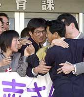 Abductees Yasushi Chimura and his wife, Fukie Hamamoto, exchange hugs with former classmates and local residents in front of a gymnasium here after seeing their hometown for the first time in 24 years.