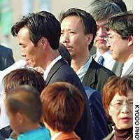 Toru Hasuike  stands behind his brother, Kaoru, after he arrived at Tokyo's Haneda airport Tuesday for his first visit to Japan from North Korea in 24 years.