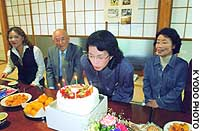 Fukie Hamamoto blows out candles on a cake from her old classmates in her hometown of Obama, Fukui Prefecture.