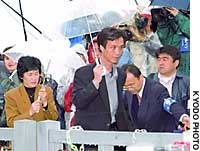 Kaoru Hasuike and his wife, Yukiko Okudo, both of whom were abducted by North Korean agents 24 years ago, pass by a throng of reporters Monday at Cape Kamomegahana in Kashiwazaki, Niigata Prefecture.