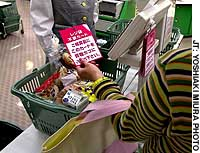 A customer at the Summit supermarket in Takaido-higashi in Suginami Ward, Tokyo, displays a card indicating she does not need any plastic shopping bags.