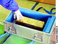An official points at the gold ingot that a burglar tried to steal Sunday from a shop in the town of Tsuna, Hyogo Prefecture.