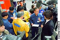 Officials in Tokyo's Chiyoda Ward explain to an offender near JR Kanda Station a new ordinance that fines those who smoke or discard cigarette butts on designated streets.
