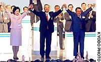 Takenori Kanzaki  (center), re-elected chairman of the New Komeito party, is applauded at a party convention in a Tokyo hall on Saturday. Kanzaki reappointed Toshiko Hamayotsu (left) as acting representative and Tetsuzo Fuyushiba as secretary general.