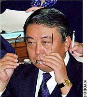 Farm minister Tadamori Oshima listens to accusations in a Lower House committee session that his former secretary took kickbacks from the construction industry.