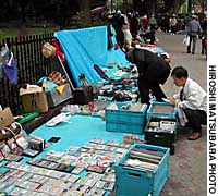Passersby rummage  through goods at stalls set up by homeless people on a sidewalk next to Yoyogi Park in Shibuya Ward, Tokyo.