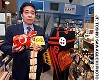 Masao Abe, director of the Fukushima Prefecture tourist office, displays some of the locally made products sold in his store in Taito Ward, Tokyo.