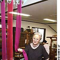 Fukumi Shimura, who weaves kimono from naturally dyed threads, displays cloth dyed with sappanwood at her workplace in Ukyo Ward, Kyoto.
