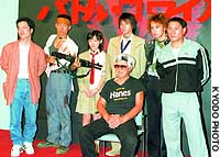 Film Director Kinji Fukasaku (sitting) poses with the author Hiroharu Takami (left) and cast of the movie 'Battle Royale' at a news conference in Tokyo in August 2000.