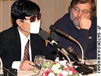 Kenki Aoyama, an escapee from North Korea, speaks at the Foreign Correspondents' Club of Japan wearing sunglasses and a mask to conceal his appearance.