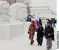 Children pass ice and snow sculptures at the annual Sapporo Snow Festival, which opened in Sapporo on Wednesday.