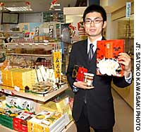 A clerk at Oidemase Yamaguchi Kan (Welcome-to-Yamaguchi Building) shows off a range of local sp@ecialties, including fugu products.