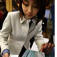A Sony Finance employee gets a ticket by flashing her Sony smart card on a self-ticketing machine at the entrance to a pop concert.