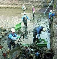 Workers remove bicycles and other discarded items from Ushigafuchi moat at the Imperial Palace.