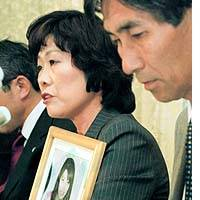 Kyoko Ino, holding a picture of her slain daughter, Shiori, and her husband, Kenichi, speak to reporters after being awarded 5.5 million yen in a damages suit.