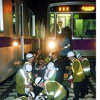Tokyo subway workers attend to simulated injuries along the train tracks during an earthquake and fire drill on the Hanzomon Line.