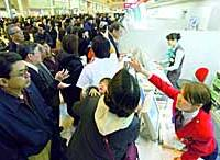 Airline staff  handle inquiries from passengers stranded Saturday morning at Haneda airport in Tokyo after a breakdown in Japan's main air traffic control system.