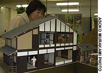 An employee of Kyoto-based Sankei Co. views the firm's miniature 'machiya' wooden house, made in one-twentieth scale.