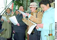 Former Korean residents of Japan who fled North Korea after going there under a repatriation program read out requests in front of the Osaka headquarters of the General Association of Korean Residents in Japan (Chongryun) in Yodogawa Ward.