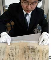 Yoji Shimada, a public relations worker at Riken, displays handwritten notes that form part of the only surviving record of that research.