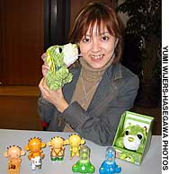 Mikako Harada of Sega Toys Co. holds Ocha-ken, a stuffed dog the company says can ease tension. Below are Takara Co.'s Gorgeous Bath masks and other 'relax-toys.'
