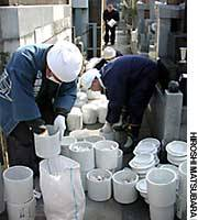 Priests and workers at Genjuin Temple in Katsushika Ward, Tokyo, transfer the ashes of 'muen botoke'' (people who died leaving no relatives) to sacks before conducting a Buddhist service for the dead Friday.