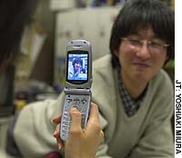A man poses for a photo taken with a camera-equipped cell phone.