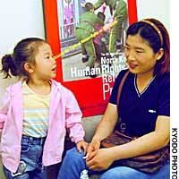 Li son Hee  and her daughter, Hanmi, two of five North Korean defectors who sought asylum at the Japanese Consulate General in Shenyang, China, in May 2002, sit before a poster showing Chinese police hauling them away from the compound.
