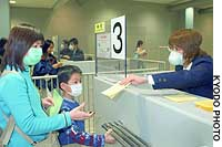 A quarantine official at Kansai International Airport hands out leaflets advising arriving passengers what to do if they exhibit SARS symptoms.