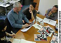Editorial staff  discuss the contents of Big Issue Kansai, a magazine to be sold on the street by homeless people, at the firm's office in Osaka's Nishi Ward. A. John Bird (center) founded The Big Issue in Britain.