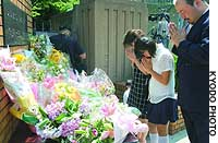 A family offers prayers to the eight children slain by a knife-wielding man in June 2001 at Ikeda Elementary School in Ikeda, Osaka Prefecture, as the school marked the second anniversary of the massacre.