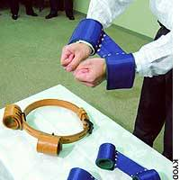 A new type of manacle unveiled at the Justice Ministry will replace leather restraining devices like the brown one on the table.