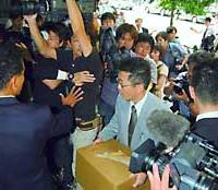 A prosecuting investigator carrying a cardboard box elbows his way past a mob of photographers and into the Osaka Securities Exchange in Chuo Ward during a raid on Friday.