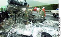 Firefighters inspect the wreckage of a car that was crushed and burned in a multiple vehicle accident on the Tomei Expressway in Shinjo, Aichi Prefecture.