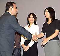 Nissan Motor Co.  President Carlos Ghosn shakes hands with Minako Kikuchi, one of the 17 recipients of a scholarship program devised by the automaker, at the firm's headquarters in Tokyo.