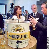 Kirin Brewery Co. officials explain the mechanism behind the firm's new self-cooling beer keg at its headquarters in Tokyo's Chuo Ward.