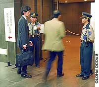 Guards stand at the entrance of Mitsui & Co.'s headquarters in Tokyo on June 27, the day of the firm's annual shareholders' meeting.