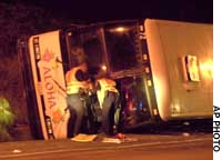 A tour bus carrying Japanese vocational school students lies on its side near Honolulu after running into a ditch Saturday night.