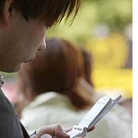 A youth accesses the Internet on his mobile phone while waiting for friends in Tokyo.