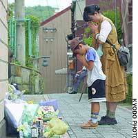 A woman and her son offer prayers at the Nagasaki parking garage where the body of a 4-year-old boy was found last week.