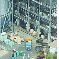 Employees mill about at a chemical plant in Matsuyama, Ehime Prefecture, after several workers fell ill due to a carbon monoxide leak.