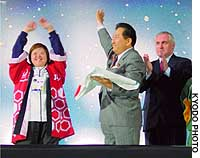 Nagano Gov. Yasuo Tanaka holds the Special Olympics flag after receiving it from Irish Prime Minister Bertie Ahern during the closing ceremony for the Summer Special Olympics held in Dublin in June.