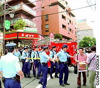 Police direct passersby away from a condominium in Tokyo's Akasaka district where four elementary school girls missing for four days were found unharmed.