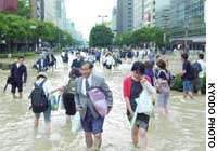 Pedestrian wade along a flooded road Saturday morning in front of JR Hakata Station
