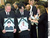 Family members hold photographs of mudslide victims Naoko Yoshigai (left) and her mother-in-law, Eiko Yoshigai, during their funeral in Minamata, Kumamoto Prefecture.