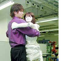 A graduate student at Tohoku University dances with a robot he helped develop at the university's campus in Sendai.