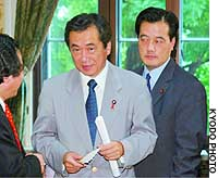 Naoto Kan (center), leader of the Democratic Party of Japan, and DPJ Secretary General Katsuya Okaya (right) emerge from a party general assembly session.