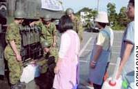 Local residents line up to receive water from Ground Self-Defense Force personnel Sunday as water services remained disrupted due to the damage from the earthquakes that hit the region the previous day.