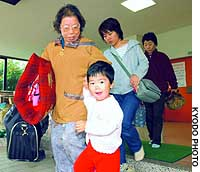 Residents taking refuge at Nango Elementary School in Miyagi Prefecture after a series of strong earthquakes prepare to move to another evacuation site Monday.